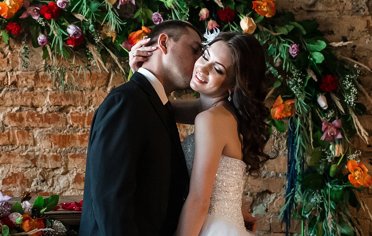 bride and groom in front of brick wall